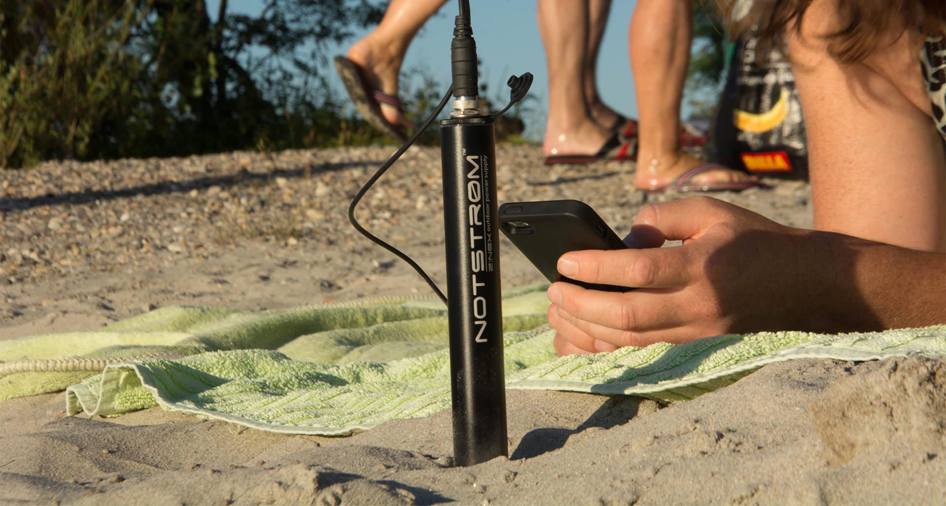 Wasser und staubdichte Powerbank Notstrøm XT im Sand eines Badestrandes